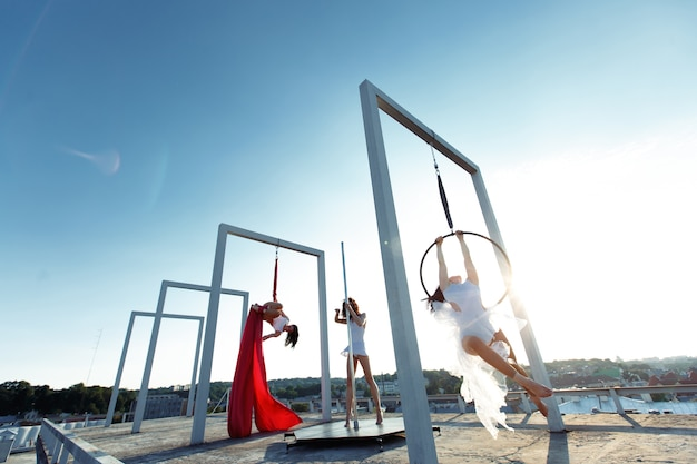 Beautiful girls performing pole, aerial and hoop dance no telhado