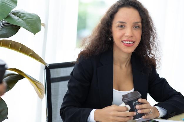 Beba café. mulher de negócios hispânica ocupada trabalhando computador portátil no escritório.