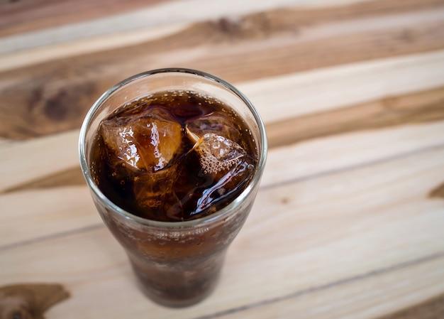 Beba cola com gelo no copo no fundo da mesa de madeira velha vintage