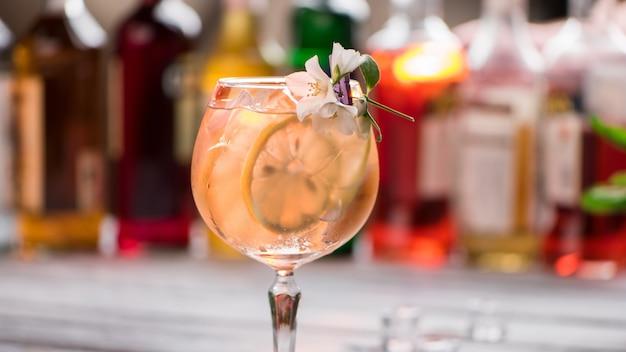 Beba com gelo em um copo de vinho. fatia de limão e cubos de gelo. tom collins decorado com flores. sinta o sabor do verão.