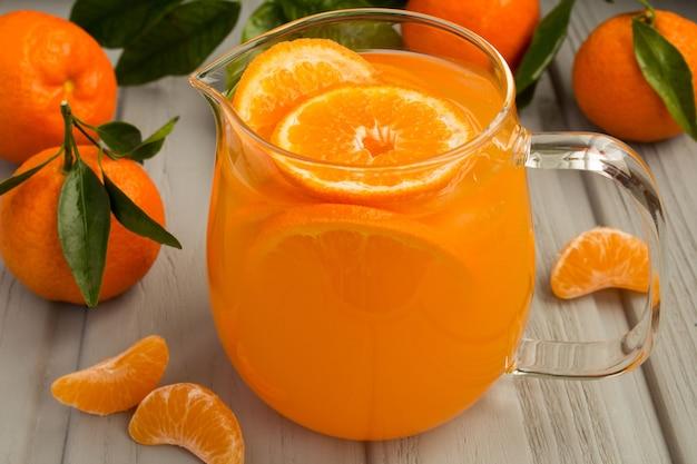 Beba com tangerinas na jarra de vidro no fundo cinza de madeira
