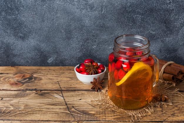 Beba de bagas de rosas selvagens com limão e canela com mel. decocção útil de vitamina de roseira. copie o espaço