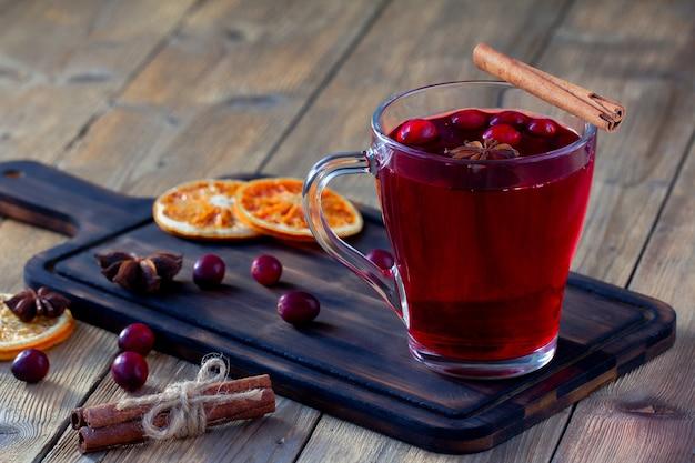 Beba de cranberries frescas em um copo sobre uma tábua de madeira escura.