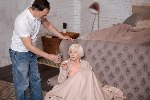 Beba. mulher idosa e doente sentada no sofá coberto com um cobertor quente e segurando o termômetro enquanto o marido servia seu copo de água.