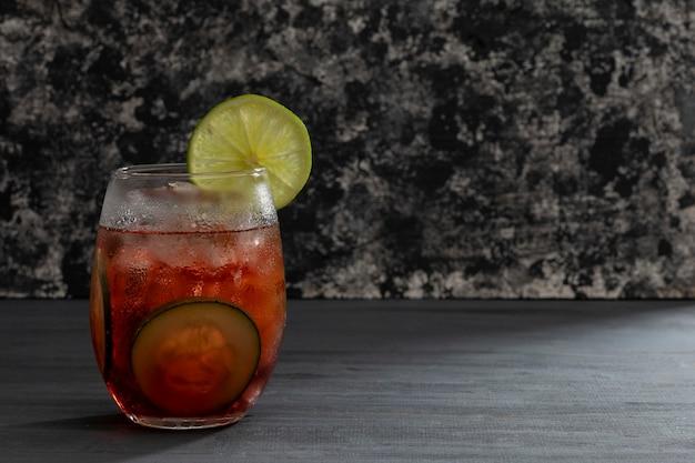 Beba ou coquetel com gelo de água mineral e pepinos fatiados em uma mesa preta