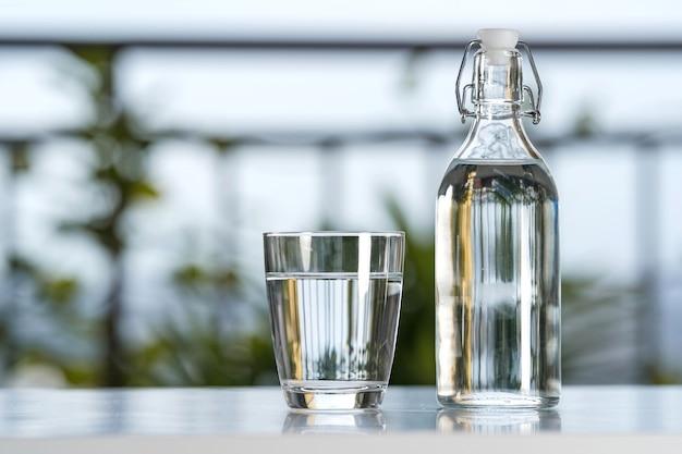 Beba uma garrafa de água com um copo na mesa no jardim de casa