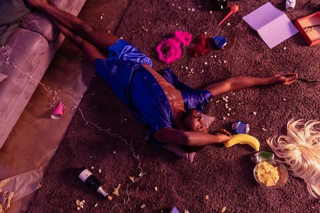 Bêbado de cabelos escuros. afro-americano emocionalmente vazio deitado no tapete escuro com lixo e sobras por toda parte