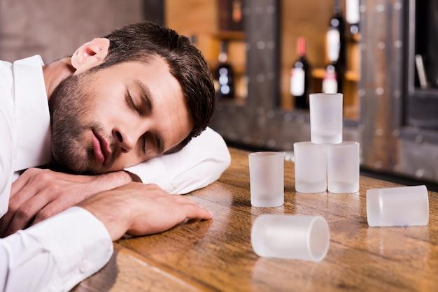 Bêbado de novo. homem bêbado de camisa branca encostado no balcão do bar e dormindo com os copos vazios em pé perto dele