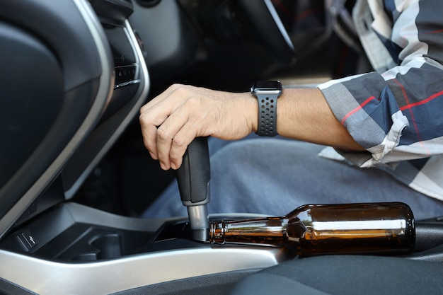Bêbado, homem, cair, sono, enquanto, dirigindo um carro, com, garrafa álcool, ao lado