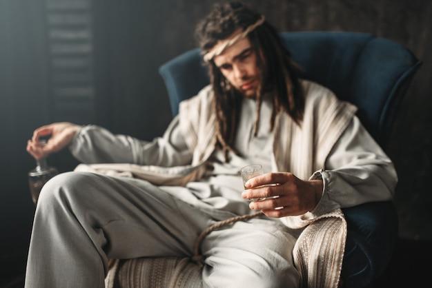 Bêbado jesus cristo segura uma pilha e uma garrafa de álcool sentado em uma cadeira.