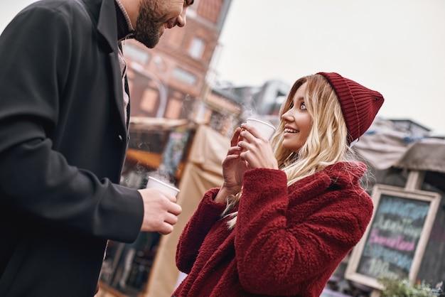 Bebam café juntos. casal jovem está falando enquanto bebe uma bebida quente, chá ou café ao ar livre