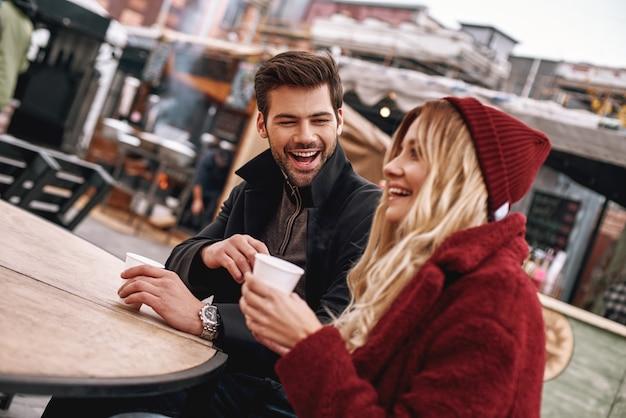 Bebam café juntos. jovem casal está falando enquanto bebe uma bebida quente, chá ou café ao ar livre. eles estão sentados no banco