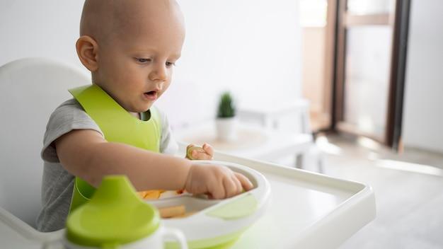 Bebê adorável brincando com comida