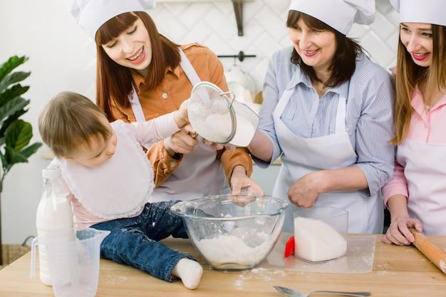 Bebê adorável com mãe, tia e avó fazendo massa com farinha e ovo e açúcar juntos em casa. mulheres de avental branco e chapéus de chef, polvilhando massa para pastelaria com farinha na mesa