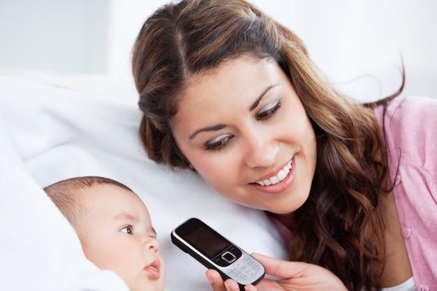 Bebê adorável com sua mãe no sofá tentando falar ao telefone