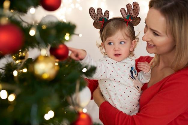 Bebê adorável e mamãe decorando árvore de natal