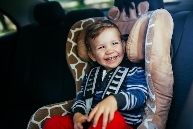 Bebé adorável em um banco de carro da segurança.