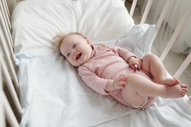 Bebê adorável feliz em roupas rosa relaxando no berço