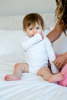 Bebê adorável sentado em uma cama com uma mulher morena, mastigando a manga