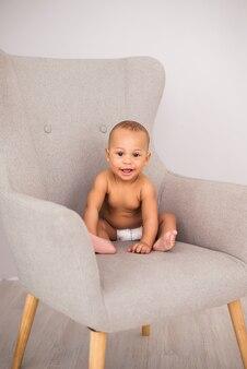 Bebê afro-americano encantador de fralda, sentado em uma cadeira.