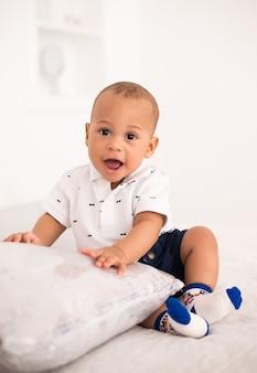 Bebê afro-americano encantador sentado na cama