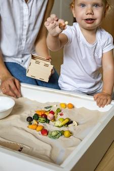 Bebê alegre e mãe brincando com pequenos brinquedos de madeira, frutas, vegetais, em casa, caixa de areia cinética