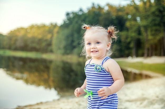 Bebé alegre que anda perto do lago.