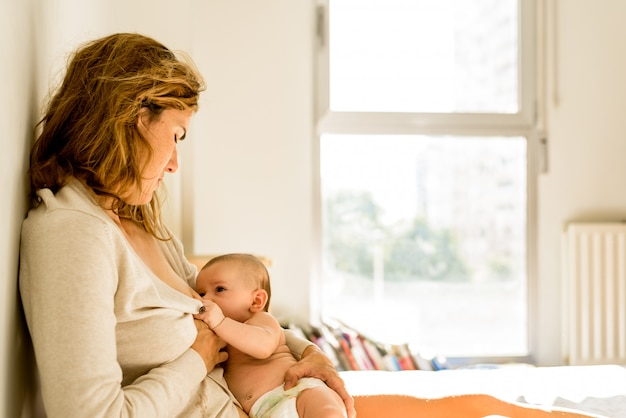 Bebê amamentado por sua mãe na cama tranquila de manhã, conceito de maternidade saudável.