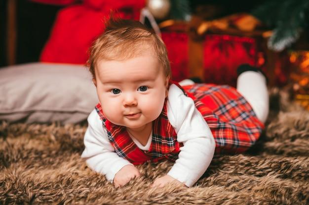 Bebê ao lado da árvore de natal
