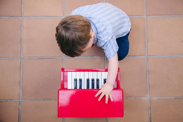 Bebê aprendendo a tocar música em casa com um piano para crianças.