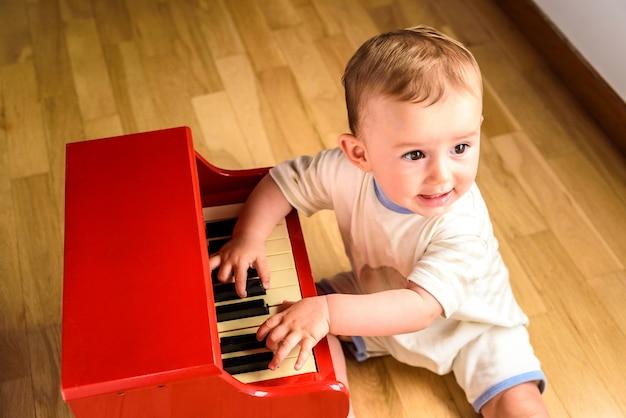 Bebê aprendendo a tocar piano com um instrumento de brinquedo de madeira, uma cena infantil tenra e engraçada.
