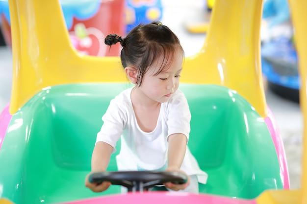 Bebê asiático bonito jogar no carro de brinquedo, terreno de jogo