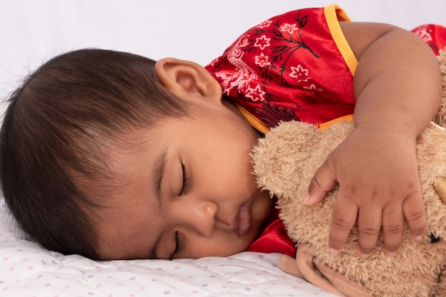 Bebê asiático bonito no vestido vermelho tradicional chinês dormindo