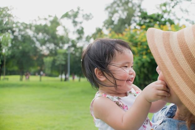 Bebê asiático bonito que sente feliz ao jogar no parque público com sua mãe.