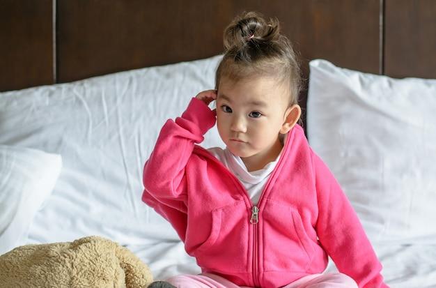 Bebê asiático bonito que veste um casaco cor-de-rosa que senta-se na cama.