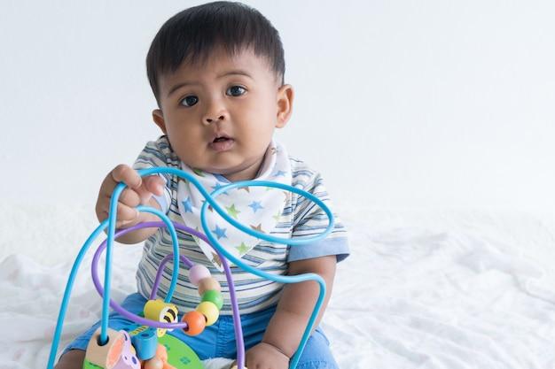 Bebê asiático bonito sentado e brincar de brinquedos de madeira