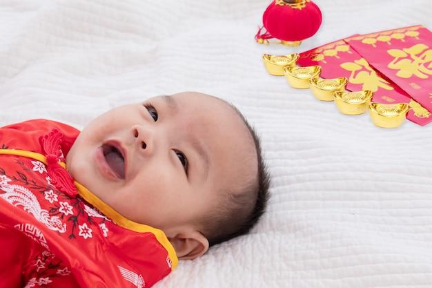 Bebê asiático bonito traje chinês cheongsam criança deitar na cama em casa com lingotes de ouro rindo bem humorado, curiosidade chinesa infantil garoto garoto olhando alguma coisa, conceito de feliz ano novo chinês
