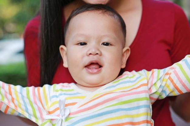 Bebê asiático do close-up que encontra-se no abraço da mãe com vista da câmera.