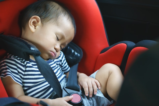 Bebê asiático dormindo no assento de carro do bebê