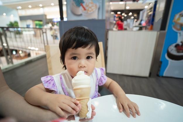 Bebê asiático fofinho tomando sorvete no restaurante