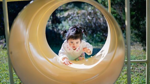 Bebê asiático fofo brincando no parquinho