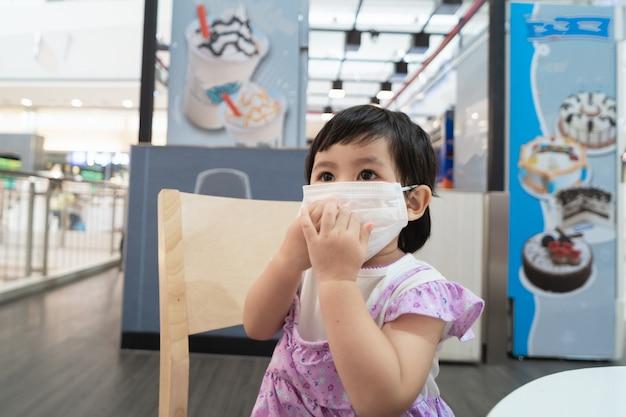 Bebê asiático fofo usando máscara cirúrgica e sentado na cadeira esperando sorvete no restaurante