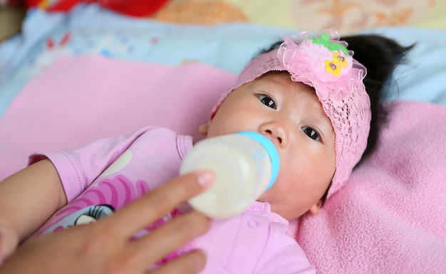 Bebê asiático infantil comendo leite da garrafa