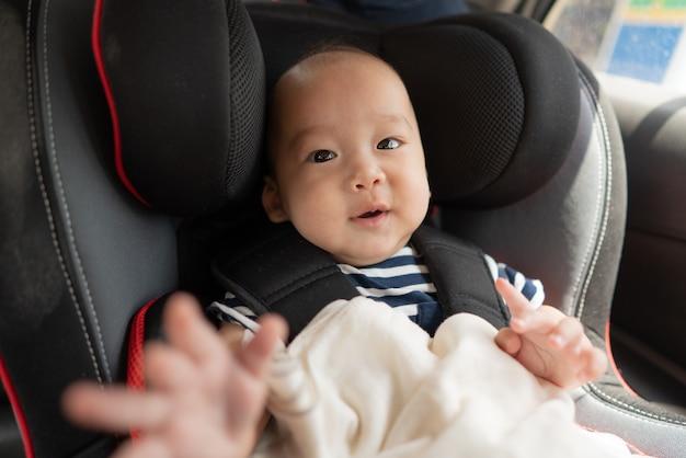 Bebê asiático na cadeirinha
