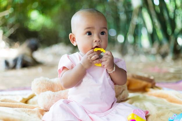 Bebê asiático pequeno bonito sentado e brinque com a felicidade selecione o foco profundidade de campo