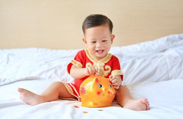 Bebé asiático pequeno de sorriso que põr algumas moedas em um banco piggy na cama.