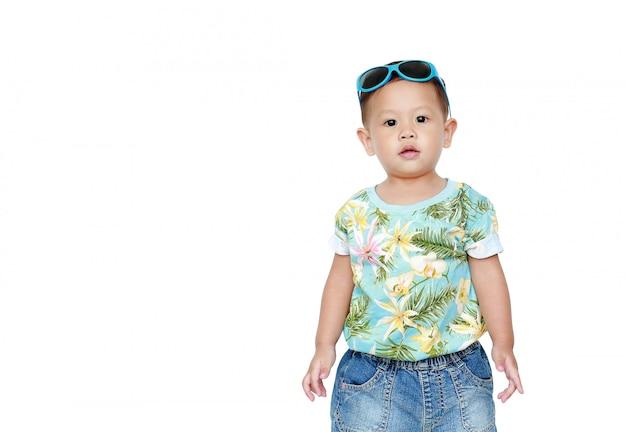 Bebê asiático pequeno do retrato que veste um vestido e uns óculos de sol do verão das flores isolados. conceito de moda e verão.