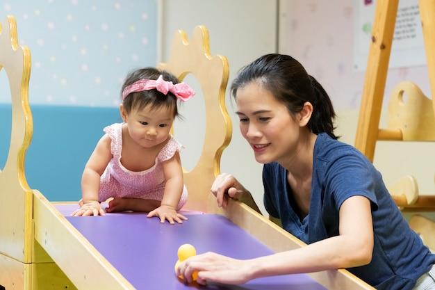 Bebê asiático pequeno novo que joga na ginástica com sua mãe