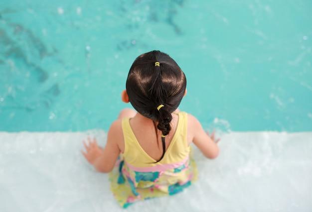 Bebê asiático pouco aprendendo a nadar