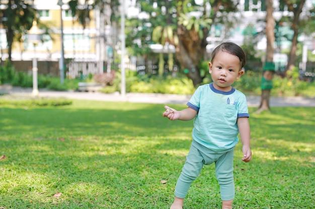 Bebê asiático que anda a primeira etapa no jardim da grama verde.